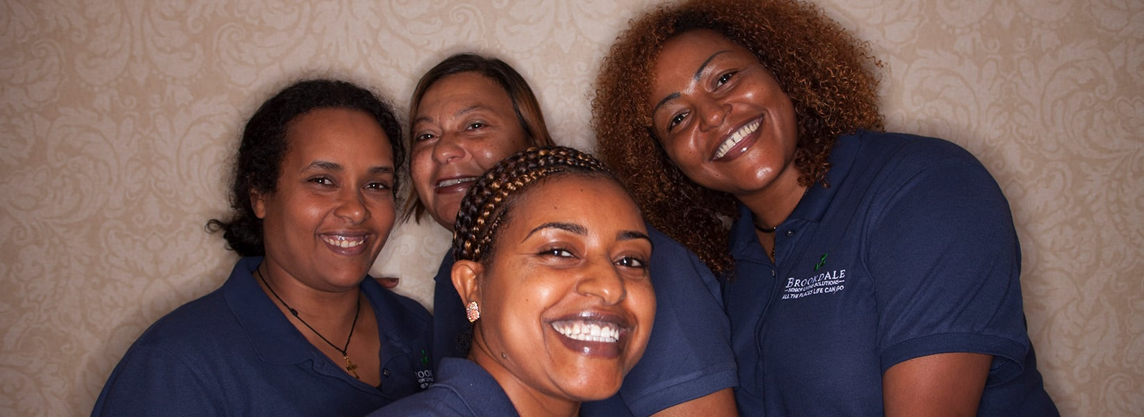 Four female Brookdale associates smiling