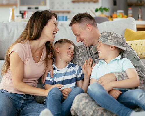veteran family on couch laughing